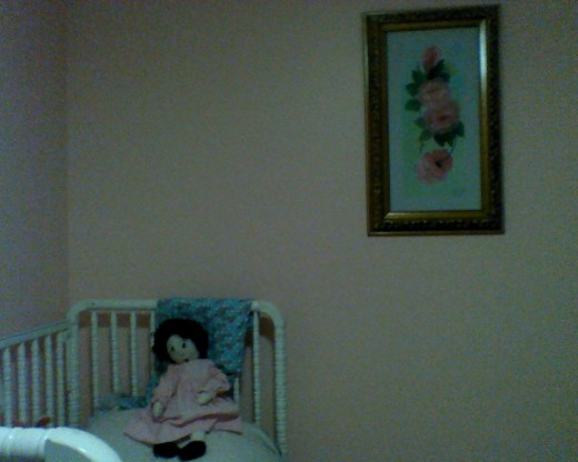 Bed, doll named Susan, and painting of pink flowers;