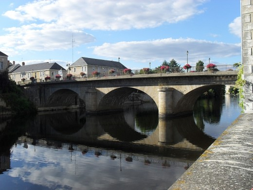 The Creuse river is crossed by two bridges, and its banks are bordered by picturesque old houses.