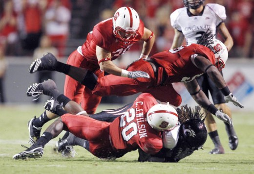 NC State defenders making a tackle against Cincinnait.