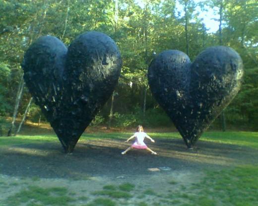 "Small person between ""Two Big Black Hearts"" by Jim Dine"