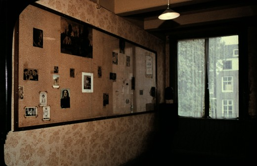 The pictures on the wall of Anne's room were placed there by Anne, now with a plastic covering for protection.   Personal photo