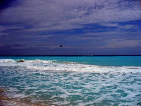 The ocean in Cancun, and someone para-sailing in the distance.