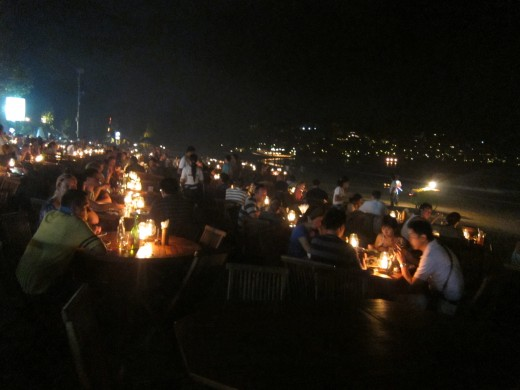 Couples, families and friends having a relaxing barbecue dinner along Jimbaran Beach, Bali