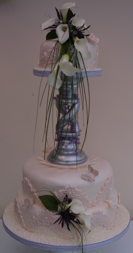 A 3 Tiered Wedding Cake with Calili Lilies and bear grass- lace pieces, butterflies and dragonflies
