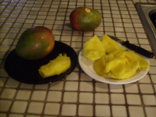 My plate of sliced fruit with seed next to a fresh mango for size comparison (note how fruit clings to the seed).