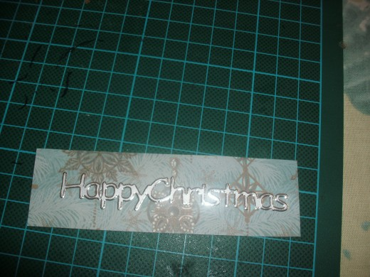 Happy Christmas sticker on card covered with contrasting paper