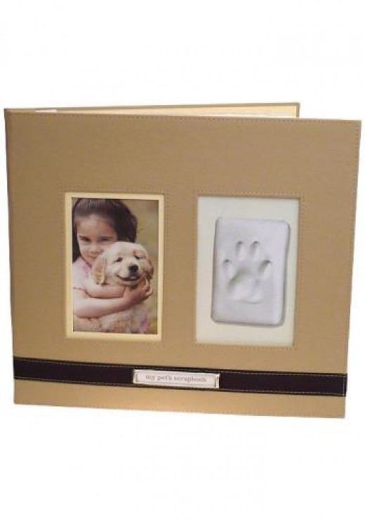 The perfect scrapbook to hold your pet's pictures and memories. Made of stitched faux leather with a ribbon accent and brushed metal name plate, scrapbook is post-bound and expandable. The cover holds a photo, your pet's paw print impression and a ke