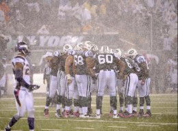 The New York Jets huddle in a driving rain during the second quarter of an NFL football game against the Minnesota Vikings on Monday, Oct. 11, 2010, in East Rutherford, N.J. (AP Photo/Bill Kostroun)