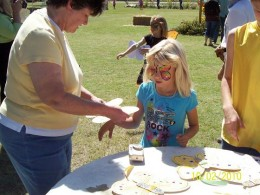 An expectant  little girl gets her butterfly decoration to wear in the Butterfly parade.