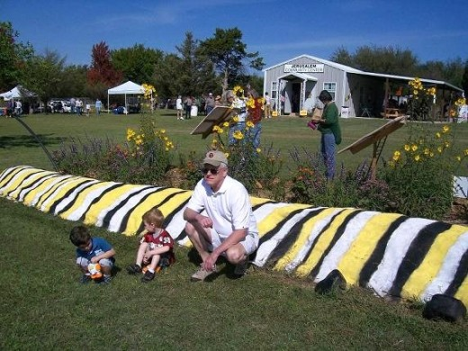 Grandpa and grand-kids enjoying the warm sunshine and Mr. Caterpillar at the Festival.