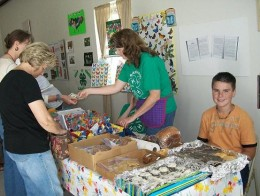 Donna, of Blanchard 4-H Club is selling some goodies to a butterfly interested person.