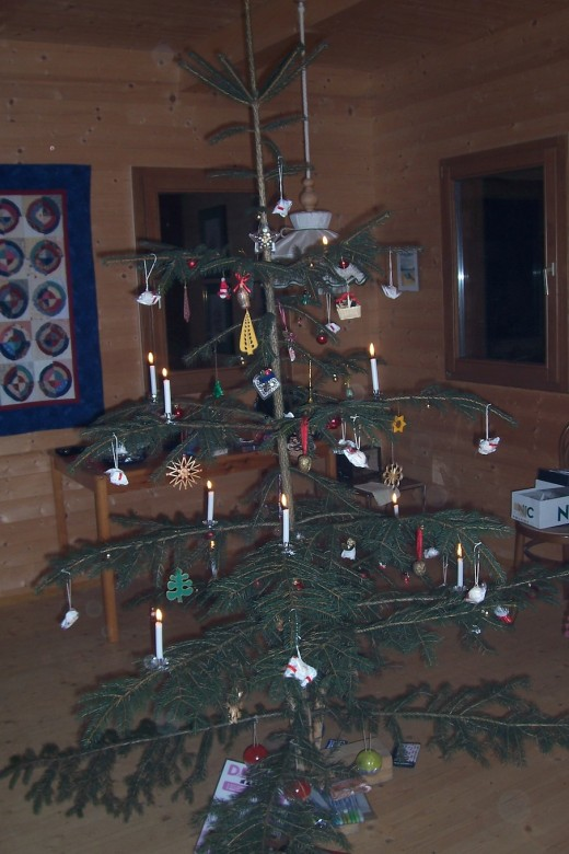 A real Christmas tree cut from the forest and decorated with ornaments and lighted candles.