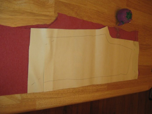Take one of your pieces of material fold it in two from sleeve to sleeve.  With the side that you want to be the outside of your pants on the inside of the fold.   Lay your pattern out on top of the material. Pin it in place.