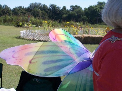 Kay Webb, Co-founder and butterfly enthusiast wears beautiful rainbow wings and a butterfly on her shoulder.