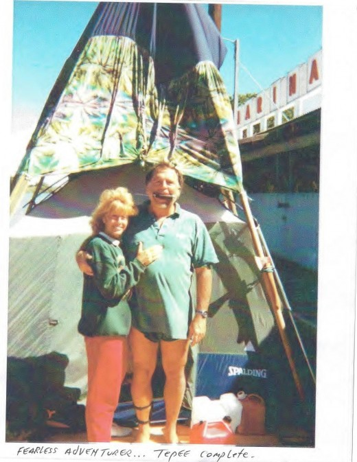 Captain Dallas with his dagger in his mouth with Tina standing in front of completed tie-dyed 20' tall teepee in Sacramento River at Freeport Boat Dock.