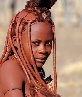 Himba (Nothern Namibia) woman covering themselves with a mixture of butter fat, ochre, and herbs to protect themselves from the sun. The mixture gives their skins a reddish tinge.