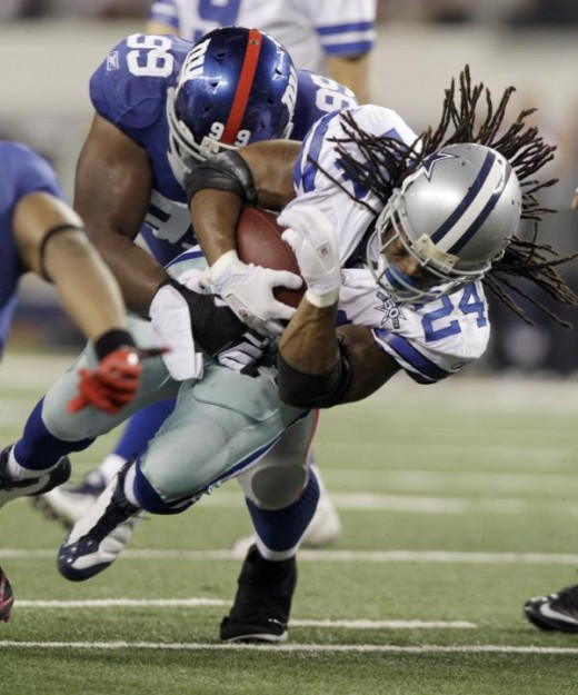 Dallas Cowboys running back Marion Barber is stopped by New York Giants defensive tackle Chris Canty during the first half of an NFL football game Monday, Oct. 25, 2010, in Arlington, Texas. (AP Photo/LM Otero)