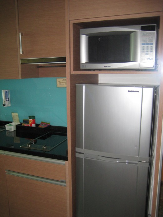 A tall fridge with freezer and microwave