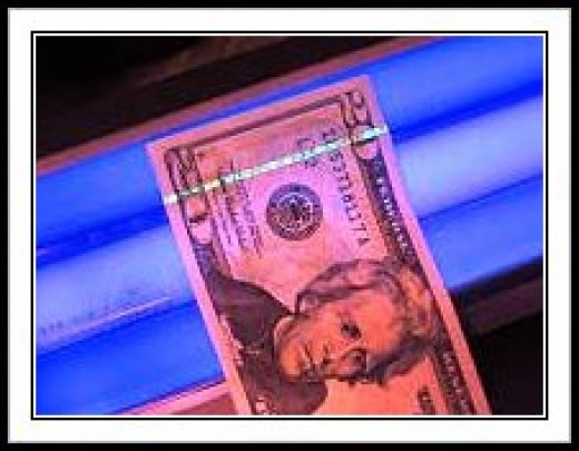 The security strip glows under a black light illustrating a security measure against counterfeiting