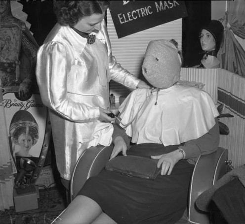 Los Angeles Coiffure Guild member wears an electric face mask for a facial ~ 1939.