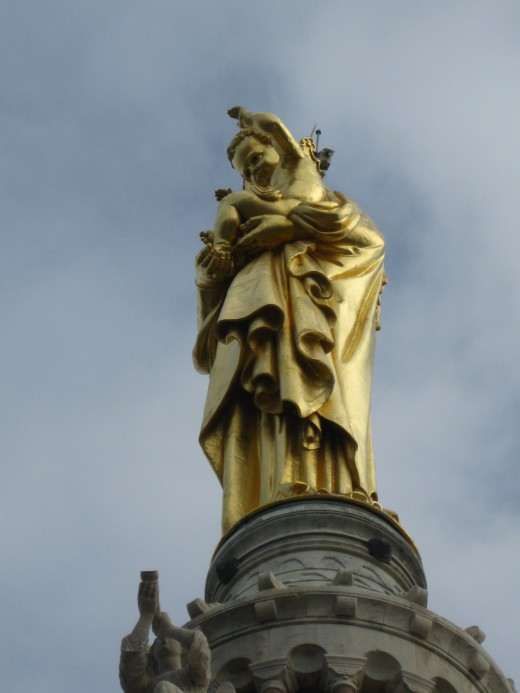Gold Statute of Virgin and Child at top of Church