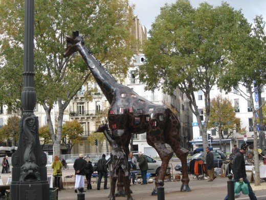 Sculpture of giraffe in an impromptu market area in center of boulevard