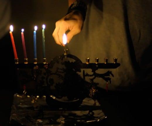 Using the shamash to light the menorah (or chanukiah) on Hanukkah