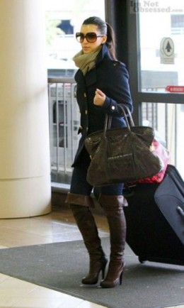 Here she is traveling with luggage yet rocking thigh boots.