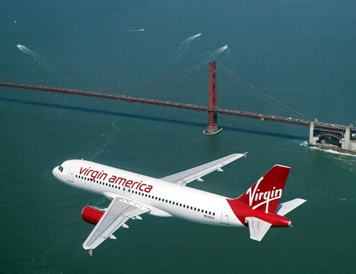 A Virgin America plane flies over San Francisco Bay and the Golden Gate Bridge.