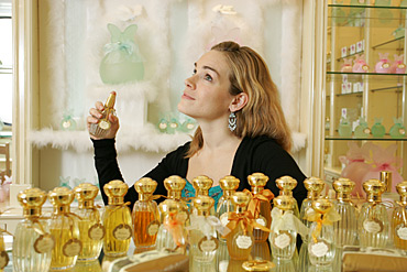 Camille Goutal spraying herself perfume.
