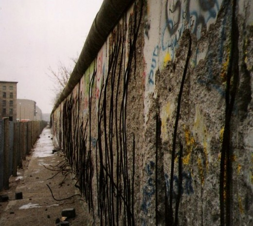 A view of the East side of the en:Berlin Wall, taken in 1990 (after the border was opened). The graffiti seen in the photo would date from after the border was opened. Most sections of the en:Berlin Wall were damaged by both local residents and touri
