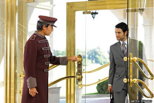 Uniformed Hotel Bus Boy Opening Door for Gentleman in a Grey Suit