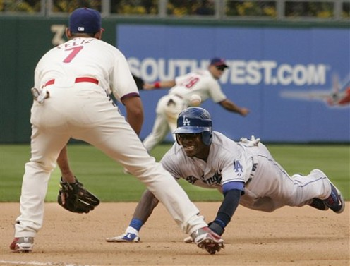 The Dodgers' Orlando Hudson, right, dives for third base ahead of the throw from the outfield to Philadelphia Phillies third baseman Pedro Feliz, left, in the eighth inning of a baseball game Thursday, May 14, 2009, in Philadelphia. The Dodgers won 5
