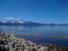 One of Tahoe's beautiful beaches with snow-capped mountains in the background.