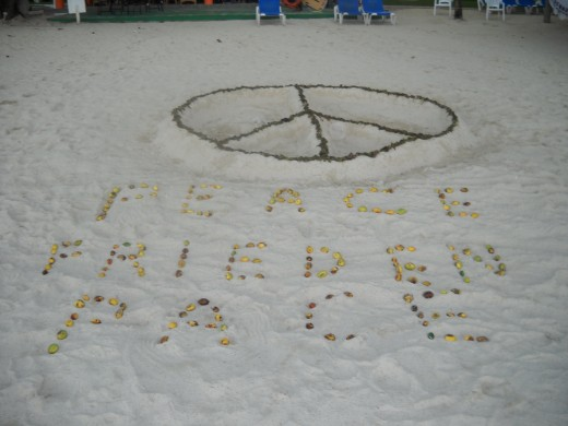 "The Bakula family made this Peace sign during a trip to Negril in 2007, dragging seaweed and fruit to write ""Peace."" We went out, and on arriving back at the beach, found it written in French and German too! It was such a touching moment!"