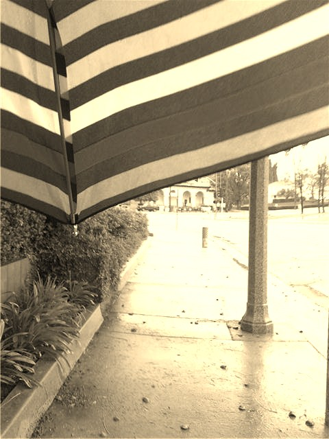 Here is a picture I took as I was walking during a light rainstorm in early 2010.  The stripes of my umbrella at the top of the photograph look quite striking in sepia.  Unfortunately this umbrella broke as I have a horrible track record with these.