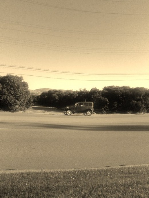 My all time favorite picture that I took of a 1930s style car driving past an orange field in 2008.  The sepia tones makes this picture look very old nostalgic.
