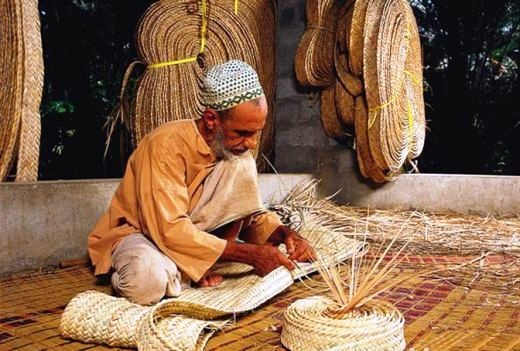 Old man weaving a mat from the date palm leaves