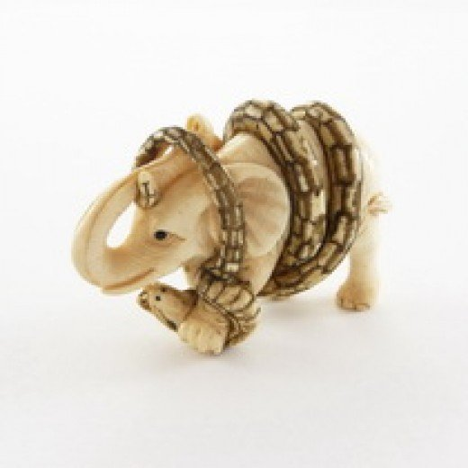 An intricate ivory netsuke of snake swallowing elephant