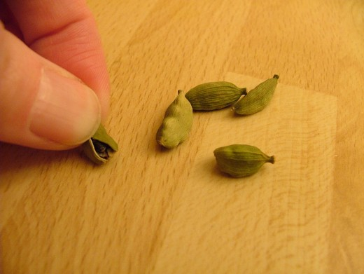 To break open the cardamom pods, hold the stem end of the pod in your fingers. Press the other end against a hard surface and the pod will split open. It doesn't need to be completely spread open, just one split will do, as shown.