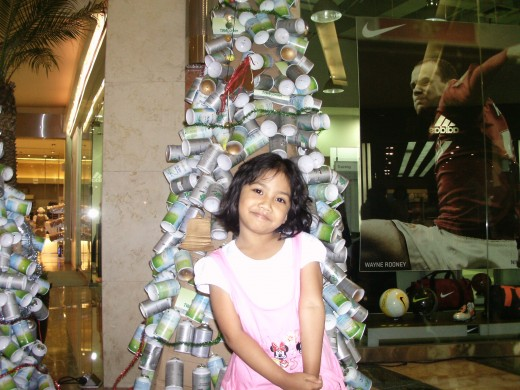 My daughter in front of one old cans Christmas tree in my local mall.