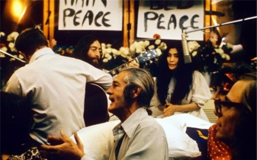"Recording ""Give Peace a Chance"". Left to right: Rosemary Leary ( face not visable), Tommy Smothers (with back to camera), John Lennon, Timothy Leary, Yoko Ono, Judy Marcioni and Paul Williams (1969) Source: Roy Kerwood"