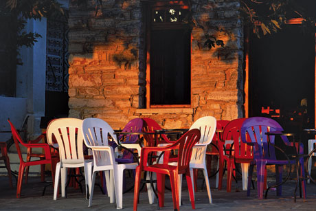 Add some pizazz to your outdoor living space by painting old white chairs with bright new colors