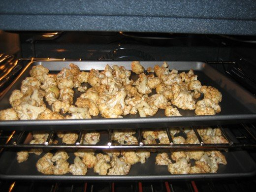 Two cookie sheets of cauliflower candy roasting in the oven.