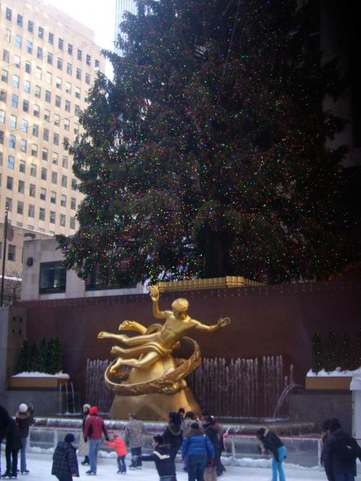 At holiday time, skaters  at the Rockefeller Center Ice Rink in Manhattan glide by a golden statue and a towering Christmas tree.