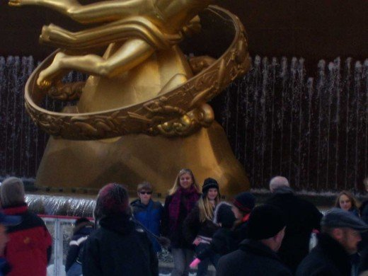 Skaters take turns posing in front of the golden statue of Prometheus.