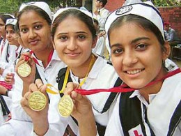 Indian girl students showing off their medals of academic excellence.