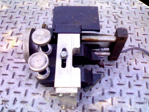 A simple calyper mount brake lathe that is used by having the cars engine drive the wheel hub to rotate it during machining. A tine electric motor drives the cutter feed very well.