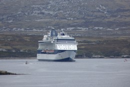 The Celebrity Infinity in Stanley Harbour with a tender carrying passengers between the ship and Stanley.