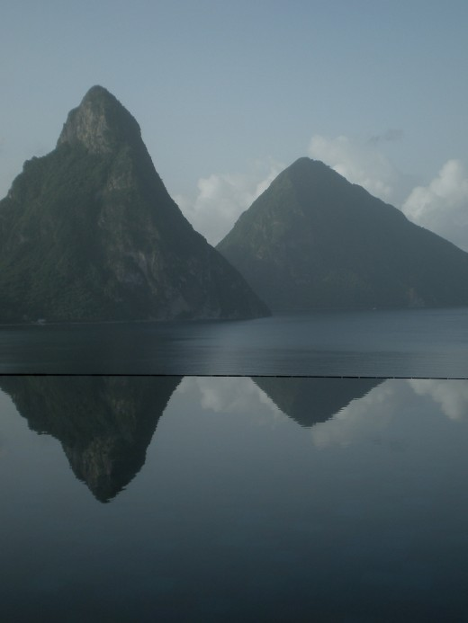 The Pitons of Saint Lucia reflected in the Infinity Pool in the Jade Club Lounge are the backdrop for a beachsun holiday.